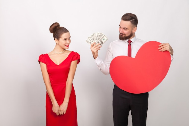 Biznesmen posiadający wiele dolarów i serca, wesoła kobieta zakłopotana. wewnątrz, studio strzał, na białym tle na szarym tle