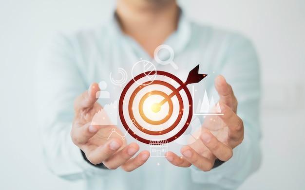 Biznesmen posiadający wirtualną tarczę ze strzałką, koncepcja celu osiągnięcia biznesowego.