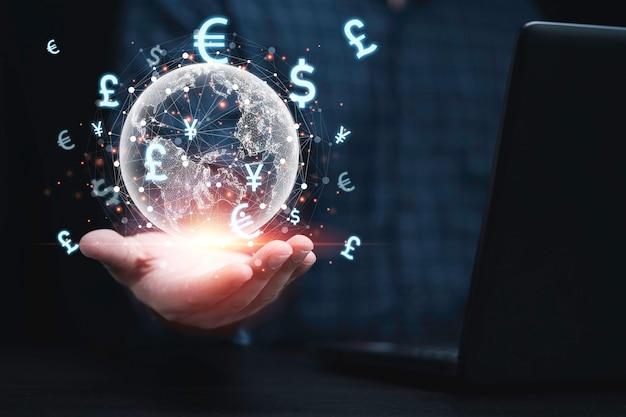 Biznesmen posiadający wirtualną ziemię ze znakiem waluty i połączenie podczas użytkowania komputera laptop handlu forex i przelew pieniędzy, koncepcja globalnej wymiany walut.