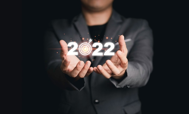 Biznesmen posiadający wirtualny 2022 z tablicą docelową do konfiguracji celu biznesowego na rozpoczęcie nowego roku.
