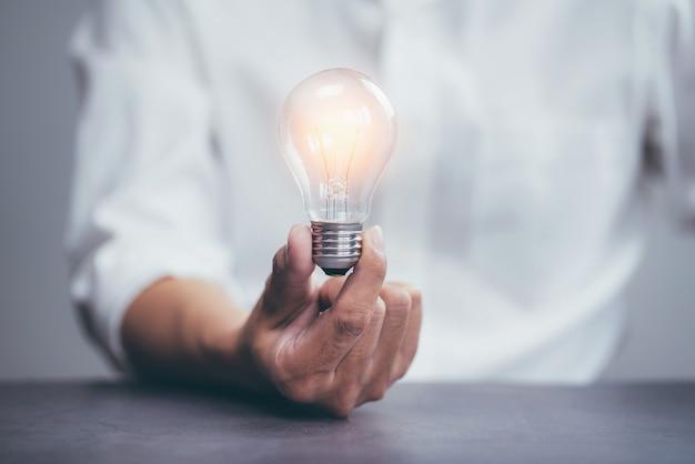 Biznesmen posiadający żarówkę jasnego światła