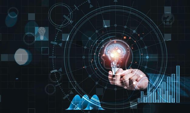 Biznesmen posiadający żarówkę z wirtualnym mózgiem i infografiką, pomysły myślenia reaktywnego i koncepcja innowacji.