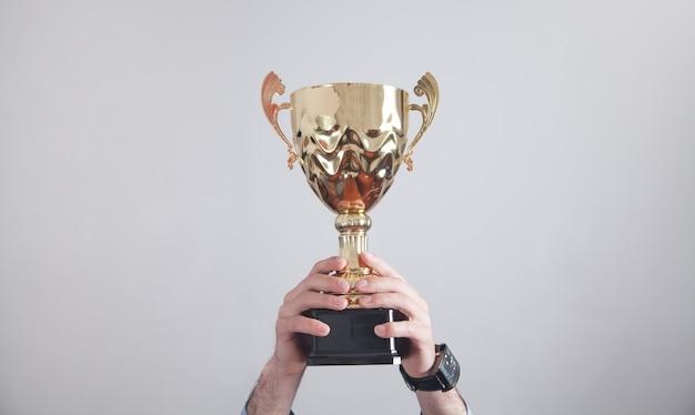 Biznesmen posiadający złote trofeum. sukces w interesach