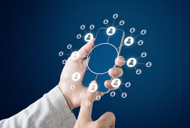 Biznesmen posiadania inteligentnego telefonu komórkowego z ikonami sieci społecznościowych