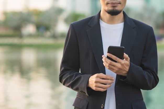 Biznesmen posiadania smartfona na zewnątrz parku miejskiego