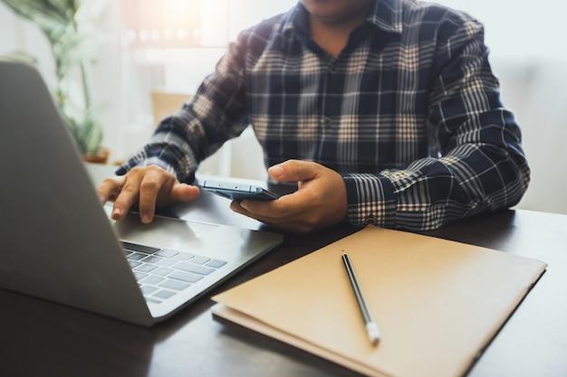 Biznesmen posiadania telefonu i korzystania z laptopa w pracy