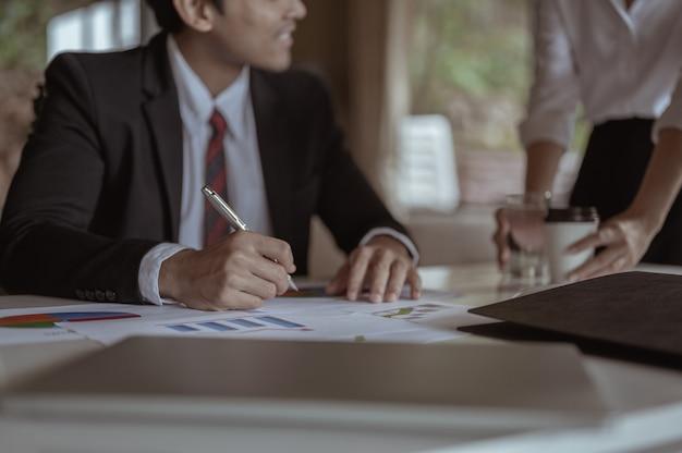 Biznesmen postanawia podpisać umowę biznesową. sekretarka podaje wodę i kawę.