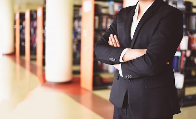 Biznesmen pozycja w biurze - mądrze biznesowego mężczyzna lub ucznia pozycja w bibliotecznym pokoju z półka na książki tła edukaci biznesowej pojęciem ludzie