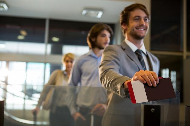 Biznesmen pozycja z kartą pokładową przy odprawa kontuarem