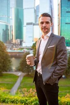 Biznesmen pozycja z kawowym kubkiem