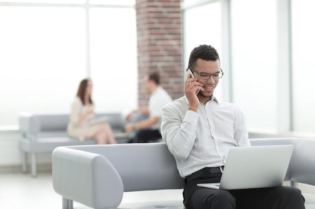 Biznesmen pracujący siedzący w holu nowoczesnego biura. ludzie i technologia