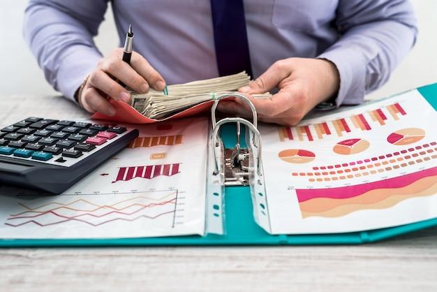 Biznesmen Pracujący W Biurze. Mężczyzna Liczy Zyski Z Wynajmu Lub Sprzedaży Towarów. Analiza Biznesowa I Koncepcja Strategii. Wykresy Biznesowe I Dokumenty Z Dolarami Na Stole. Premium Zdjęcia