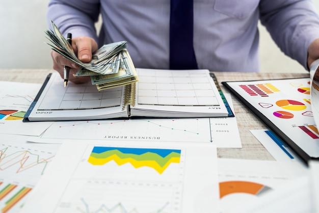 Biznesmen pracujący w biurze. mężczyzna liczy zyski z wynajmu lub sprzedaży towarów. analiza biznesowa i koncepcja strategii. wykresy biznesowe i dokumenty z dolarami na stole.