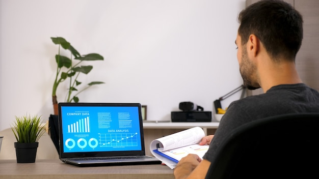 Biznesmen pracujący w biurze z laptopem. dokument na jego biurku. zmotywowany mężczyzna