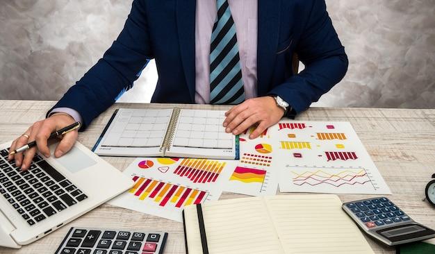 Biznesmen pracujący w biurze z wykresami biznesowymi, laptopem i notatnikiem.