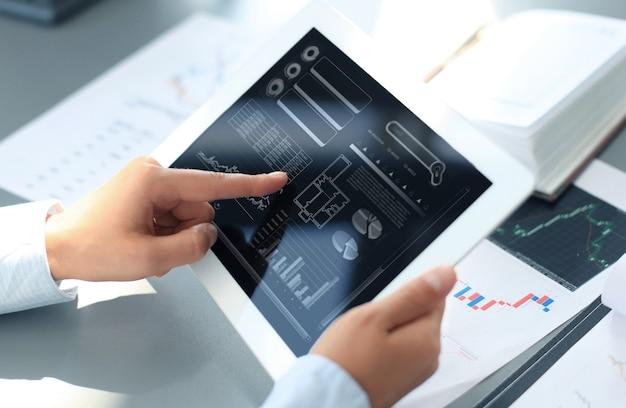 Biznesmen pracujący z cyfrowym tabletem na drewnianym biurku jako koncepcja