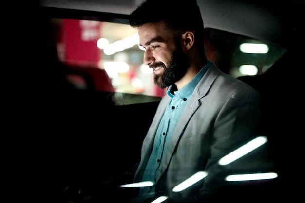Biznesmen pracuje do późna w samochodzie kończy swoją pracę. ciężka praca w godzinach nadliczbowych w drodze do domu.