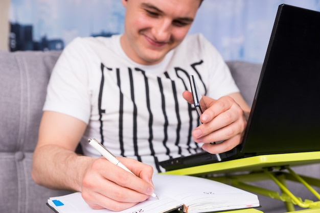 Biznesmen pracuje na laptopie i robi interesy z domu, siedząc na kanapie, trzymając długopis i telefon komórkowy