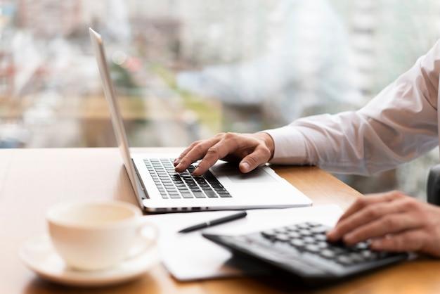 Biznesmen pracuje na laptopie i robi obliczeniom