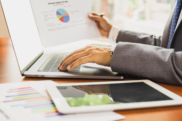 Biznesmen pracuje na laptopie i trzyma papierowego wykresu pieniężnego diagram.