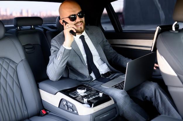 Biznesmen pracuje na laptopie na tylnym siedzeniu samochodu wykonawczego
