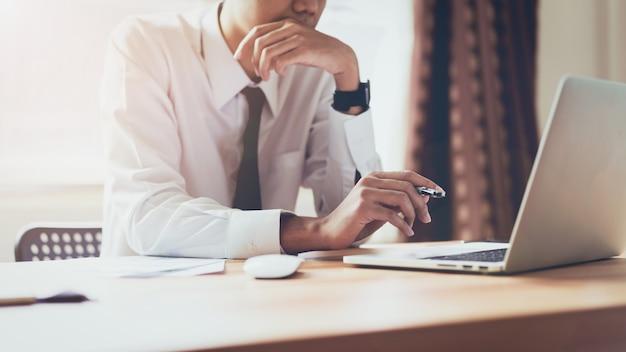 Biznesmen pracuje na laptopie przy biurowym pokojem projektów pomysły. vintage ton.