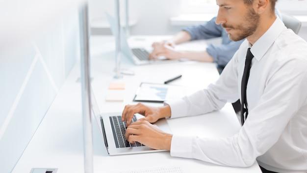 Biznesmen pracuje na laptopie w biurze. zdjęcie z miejscem na kopię.