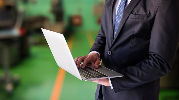Biznesmen pracuje na laptopie w fabryce