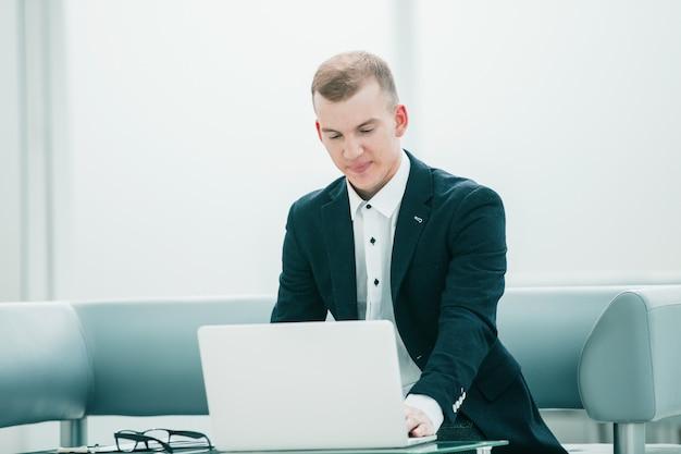 Biznesmen pracuje na laptopie w holu nowoczesnego hotelu. ludzie i technologia