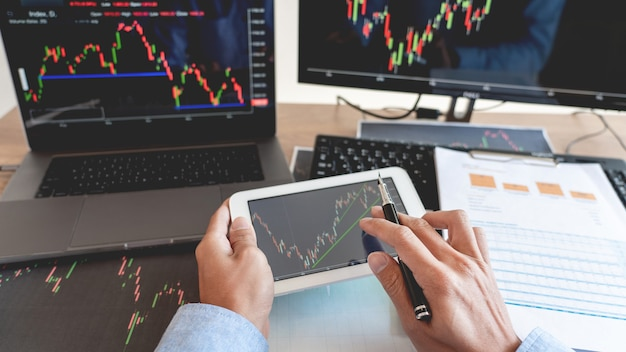 Biznesmen pracuje na rynku forex z laptopem i tabletem