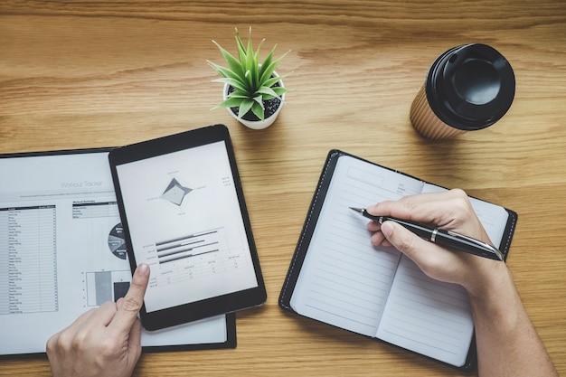 Biznesmen pracuje na wykresu dokumentu pieniężnym raporcie z cyfrową pastylką