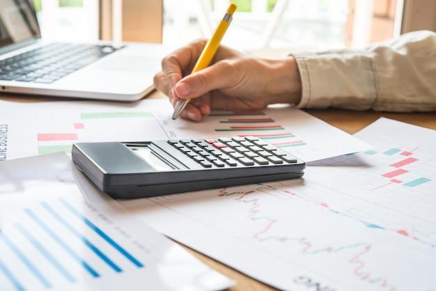 Biznesmen pracuje przy biurem z dokumentami i wykresami