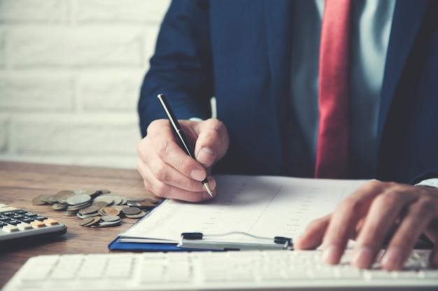Biznesmen pracuje przy komputerem i dokumentem