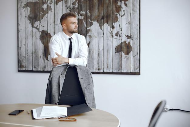 Biznesmen pracuje w biurze. mężczyzna odwraca wzrok. facet stoi przy mapie