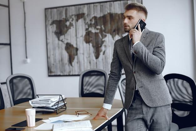 Biznesmen pracuje w biurze. mężczyzna rozmawia przez telefon. facet w garniturze