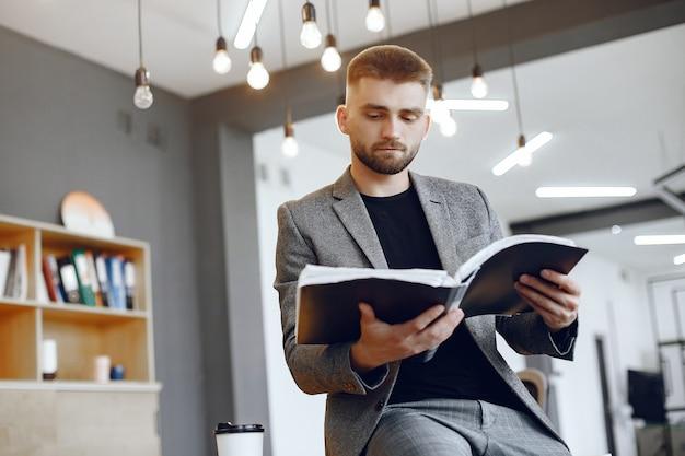 Biznesmen pracuje w biurze. mężczyzna trzyma folder. facet siedzi w biurze