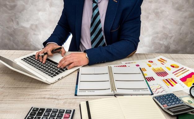 Biznesmen pracuje w biurze z biznesowymi wykresami, laptopem i notatnikiem.