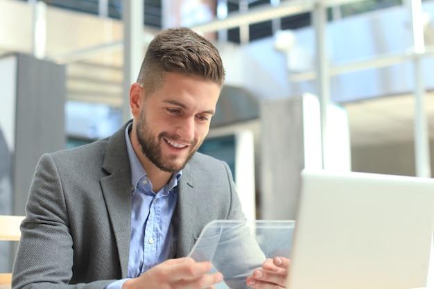 Biznesmen pracuje w biurze z przezroczystego tabletu i laptopa.