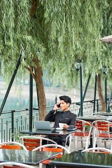 Biznesmen pracuje w kawiarni na świeżym powietrzu