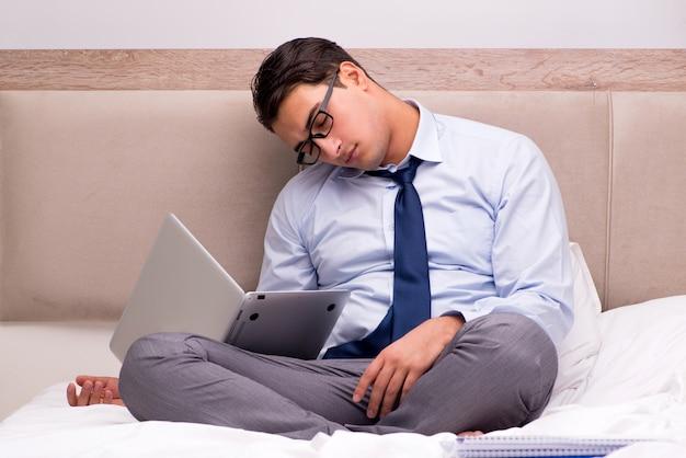 Biznesmen pracuje w łóżku w domu