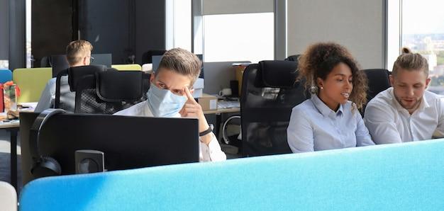 Biznesmen pracuje w prewencyjnej masce medycznej w epidemii w biurze, koledzy w tle.