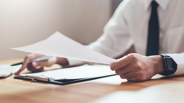 Biznesmen pracuje w swoim biurze z dokumentami i sprawdzić dokładność informacji.
