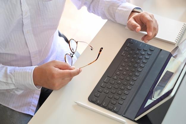 Biznesmen pracuje z cyfrowym pastylka komputerem i mądrze klawiaturą