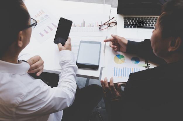 Biznesmen pracuje z dokumentem, smartphone i cyfrową pastylką przy biurem