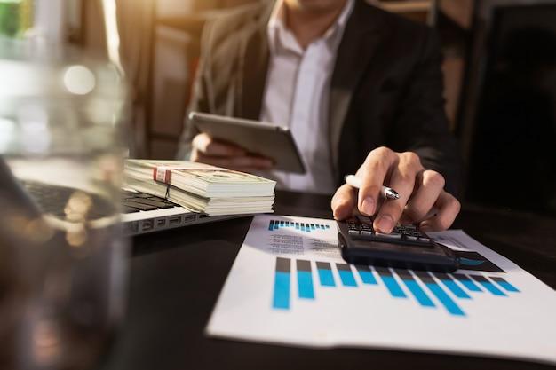 Biznesmen pracuje z finansami na temat kosztów i kalkulatora