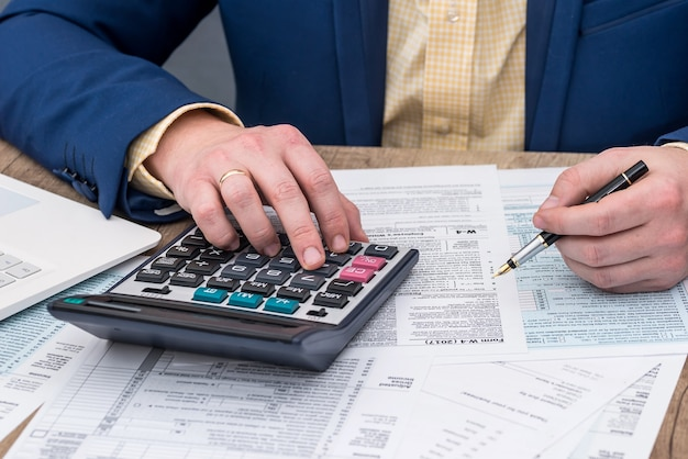 Biznesmen pracuje z formularzem podatkowym w-4 i kalkulatorem