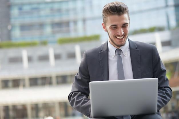 Biznesmen pracuje z laptopem na zewnątrz budynku biurowego