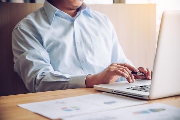 Biznesmen pracuje z laptopem w otwartej przestrzeni biurze