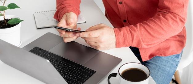 Biznesmen pracuje z laptopem zdalnie lub komunikuje w ogólnospołecznej sieci siedzi w domu