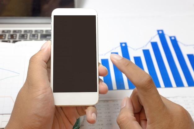 Biznesmen pracuje z pustego ekranu smartphone przy biurem.